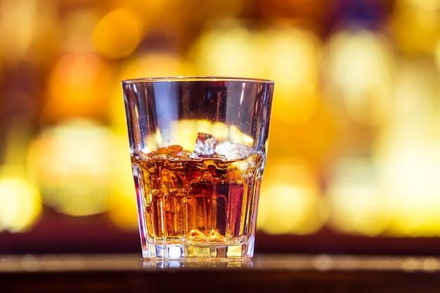 One whiskey with ice in a glass on the bar (closeup). traditionally irish drink