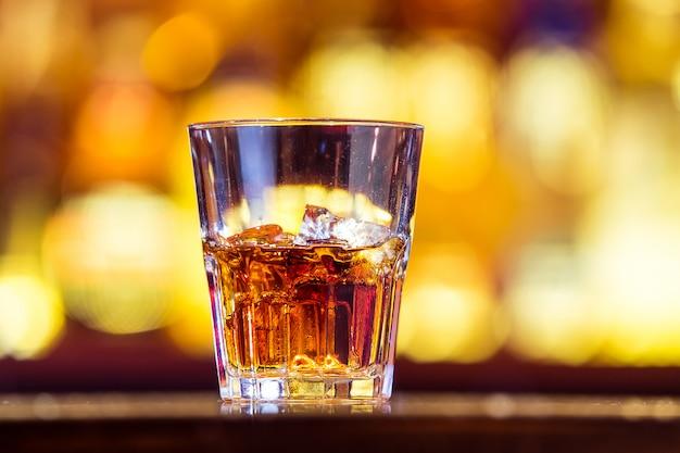 Один виски со льдом в стакане на баре (крупным планом). традиционно ирландский напиток