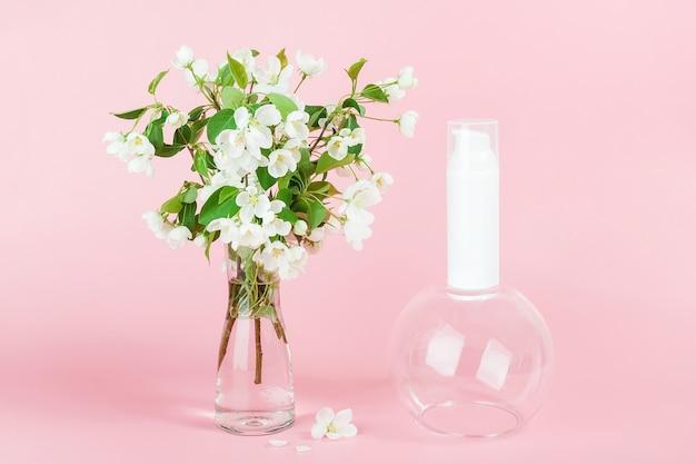 ピンクの背景に花瓶の1つの白い空白の化粧品チューブボトルと咲く枝。ナチュラルオーガニックスパコスメティックビューティーコンセプト