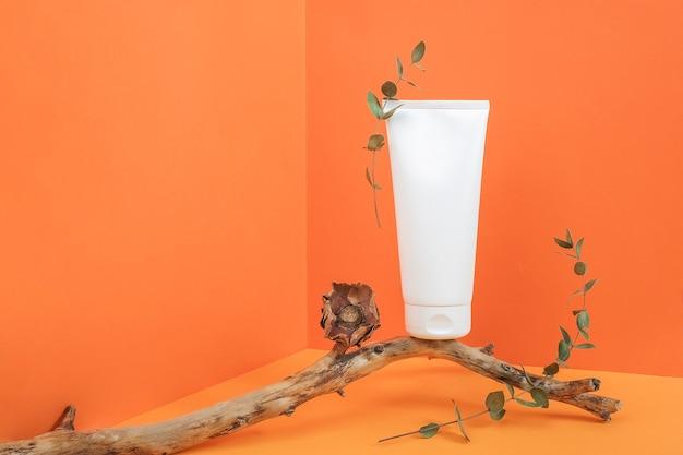 オレンジ色の背景のコーナースペースにドライフラワーとユーカリの枝と木の棒の上の1つの白い空白の化粧品チューブボトル。モックアップ正面図コピースペース。