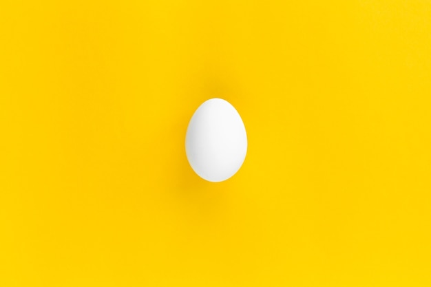 One white chicken egg is centered on a yellow background. healthy organic food and diet concept