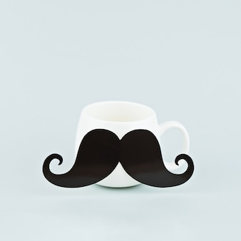 One white coffee mug with large black mustache on blue background