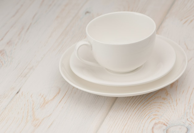 One white cup and saucer on old wooden board