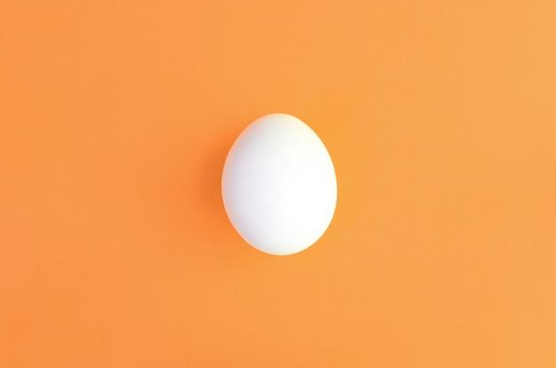 One white easter egg on a bright orange