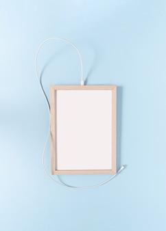 パステルブルーの背景にusbケーブルを備えた1つの白いフレーム最小限のクリエイティブコピースペース