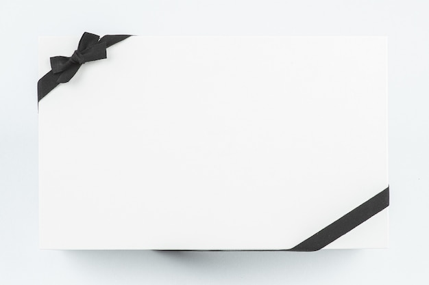 One white gift box decorated with a black ribbon