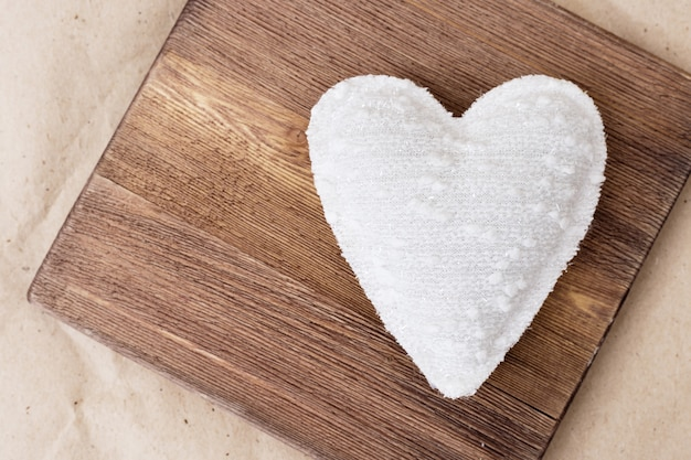 One white heart made of cloth placed on retro wooden board