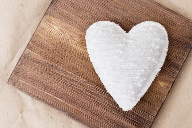 レトロな木の板に置かれた布で作られた1つの白いハート