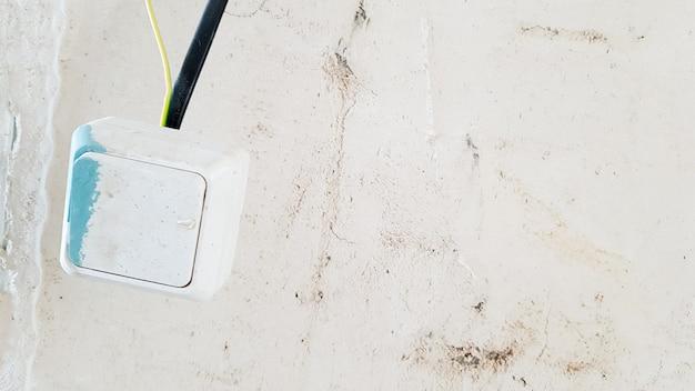 Один белый выключатель света в краске и шпатлевке временно висит на черном проводе во время ремонта на фоне недостроенной стены. разомкнуть провода.