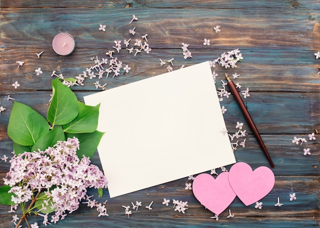 Одна белая бумага, сирень, фиолетовая свеча, чернильная ручка и два розовых сердца на старинных деревянных фоне