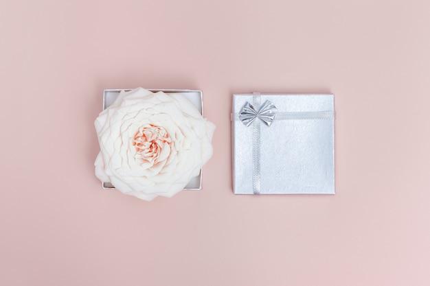 하얀 장미 꽃 1 개와 반짝이는 작은 선물 홀리데이 미니멀 컨셉 컬러 트렌드