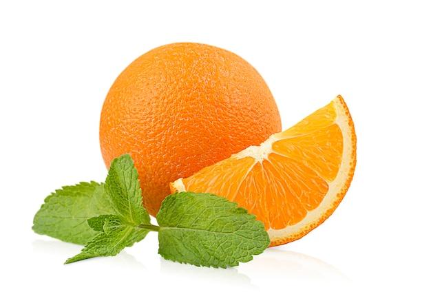 격리된 흰색 배경에 민트 잎이 있는 전체 및 오렌지 조각 1개