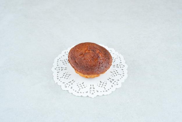 白いテーブルの上の1つの全体のおいしい甘いカップケーキ。