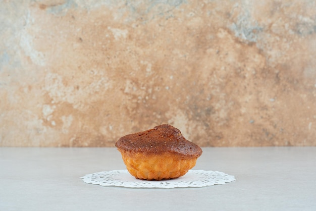 One whole delicious sweet cupcake on white table.