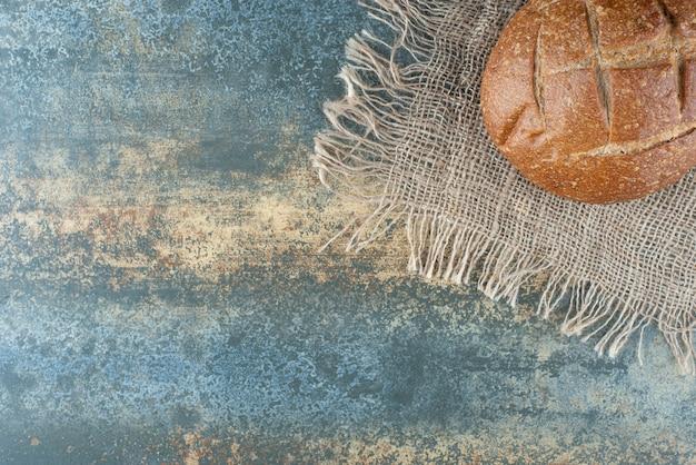 Un intero panino marrone fresco su tela di sacco