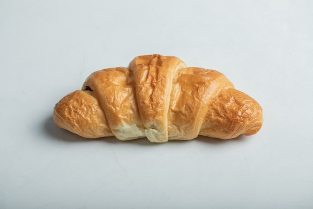 One whole fresh delicious croissant on a white background.