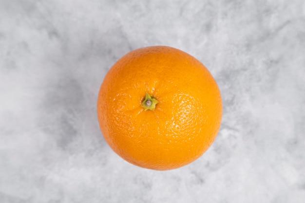 One whole fresh juicy orange fruit placed on marble
