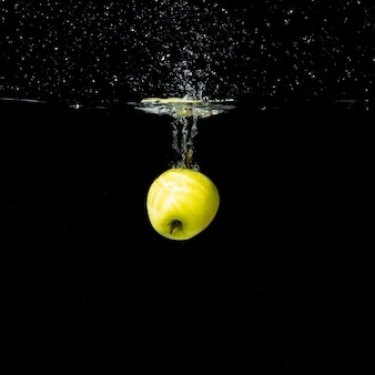 One whole green apple splashing into water against black background