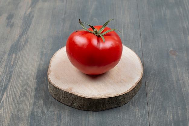 Один целый сочный помидор на деревянном столе
