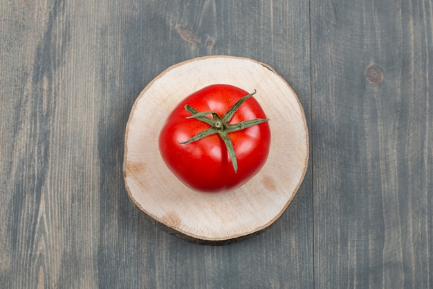 One whole juicy tomato on a wooden table