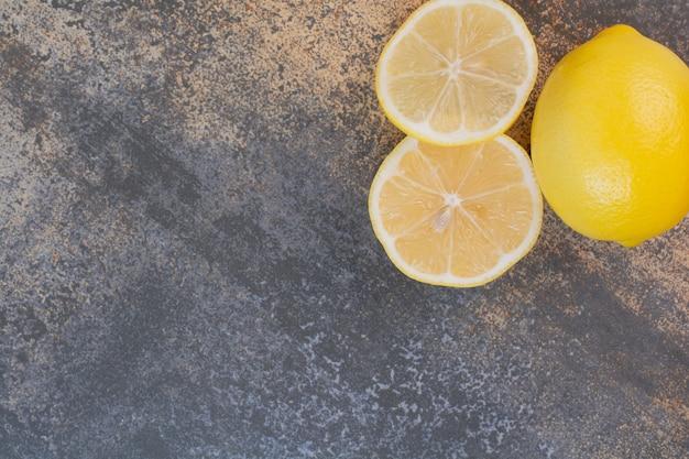 Un limone intero con fette sulla superficie della pietra