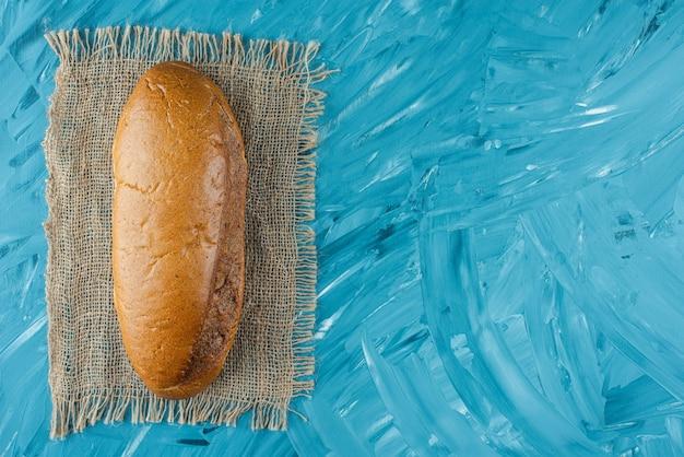 Una pagnotta intera di pane fresco bianco su tela di sacco su sfondo blu.