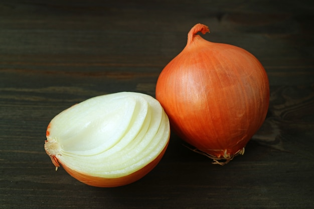 One whole onion with one cut in half isolated on dark brown background