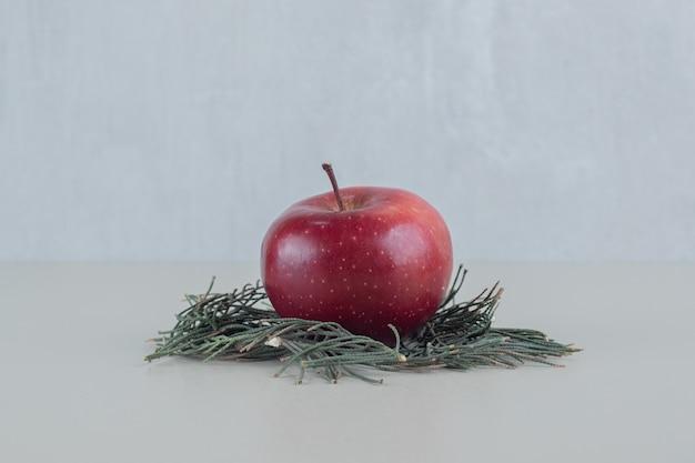 Una mela fresca rossa intera su sfondo grigio.