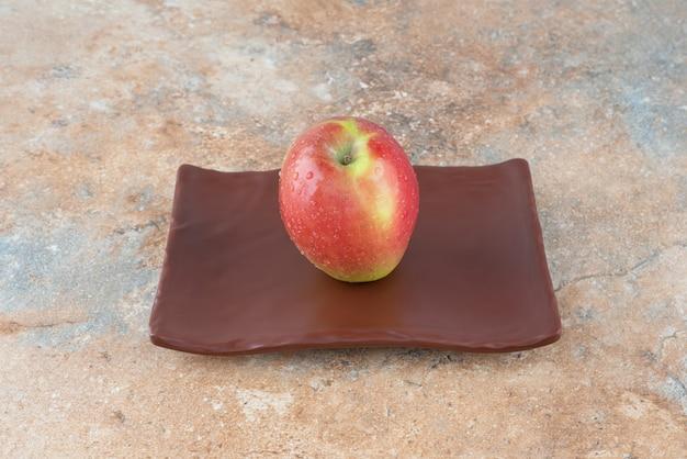 Одно целое красное сладкое яблоко на темной тарелке.