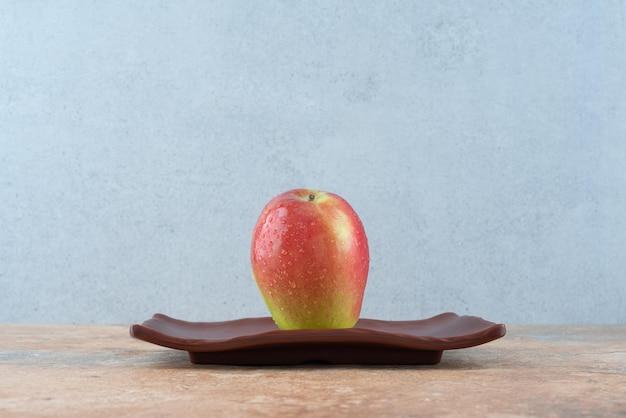 Одно целое красное сладкое яблоко на темной тарелке