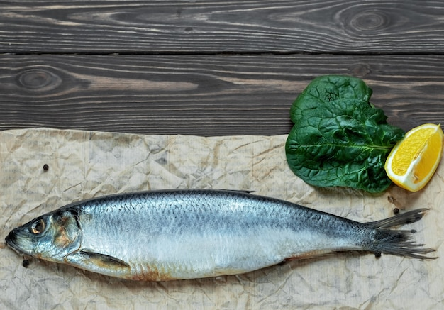 One whole salted atlantic herring on parchment paper, next to spices, lemon and lettuce leaf