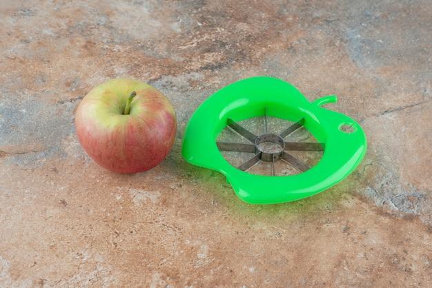 Одно целое сладкое яблоко с инструментом для очистки на мраморном столе.