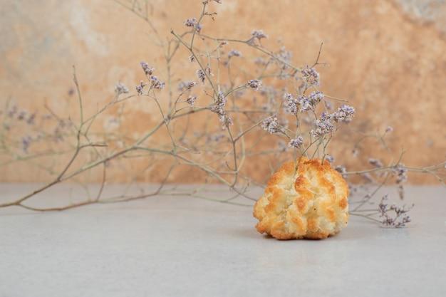 Один цельный сладкий кекс с увядшим цветком
