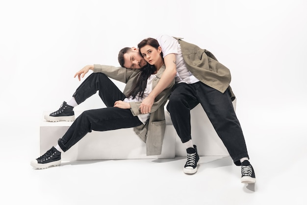 One whole. trendy fashionable couple isolated on white studio background. caucasian woman and man posing in basic minimal stylish clothes. concept of relations, fashion, beauty, love. copyspace.