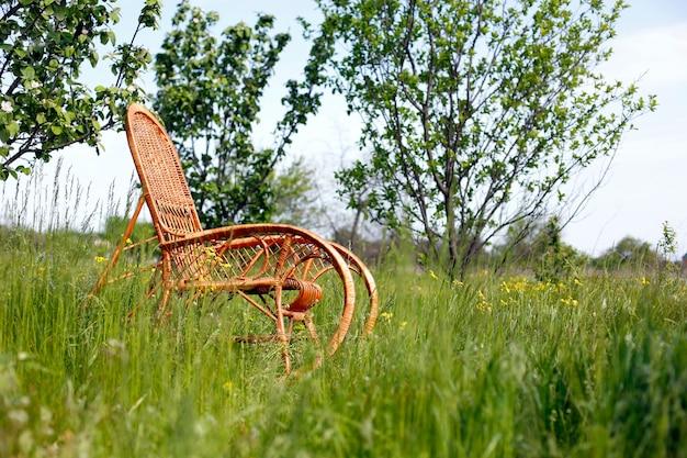 녹색 자연 배경에서 하나의 고리 버들 흔들 의자 휴식