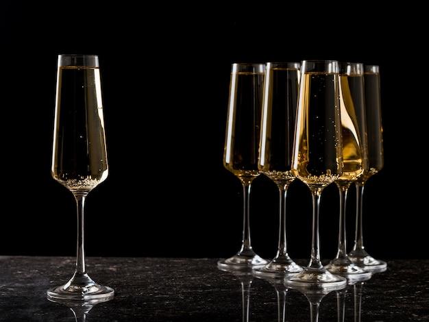 Один бокал с вином стоит отдельно от других. популярный алкогольный напиток.
