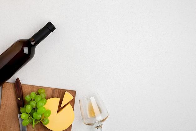 Один бокал с белым вином, бутылка белого винного сыра на белом фоне, горизонтальный вид из ...