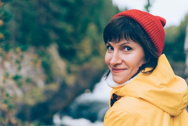 自然との一体感。滝の近くでカメラを見ている笑顔の女性の背面図、