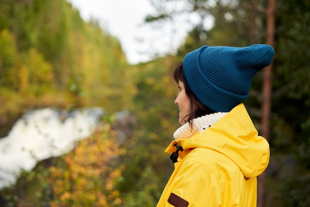 Один с природой. вид сзади до неузнаваемости женщины, глядя на лес и водопад