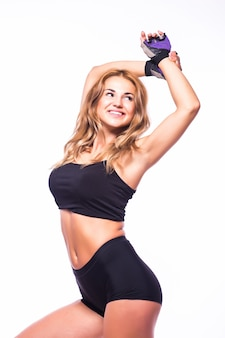 Una donna che esercita fitness zumba ballando in silhouette sul muro bianco