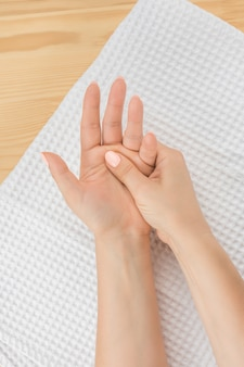 한 여성의 손은 손바닥이 위로 향하게 하얀 수건에 누워 다른 손을 마사지합니다. 사람의 근접 촬영 손 흰색 배경에 건강 개념에서 고통에서 그녀의 손을 마사지.
