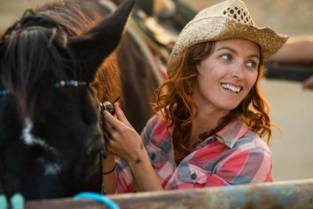Одна женщина на ферме или на ранчо, ухаживающая за своей лошадью, улыбается и веселится