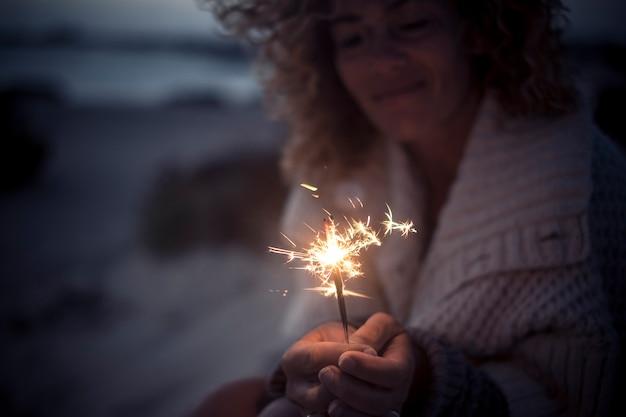 一人の女性が屋外で線香花火の光を見て祝う