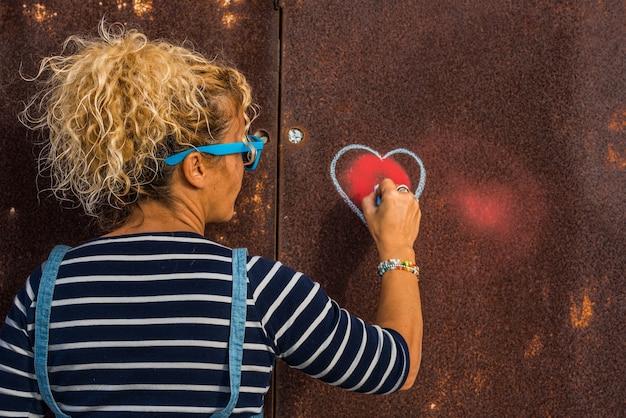 Одна женщина рисует сердце на стене на улице - кудрявая женщина показывает свои эмоции