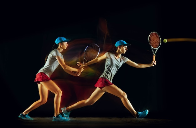 One woman playing tennis in different positions isolated on black wall in mixed and stobe light