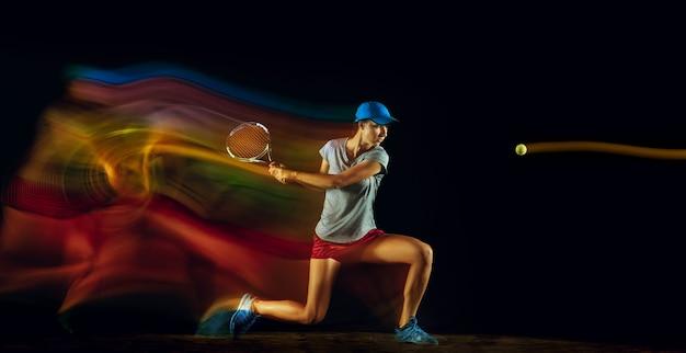 Una donna che gioca a tennis isolata sul muro nero in luce mista e stobe
