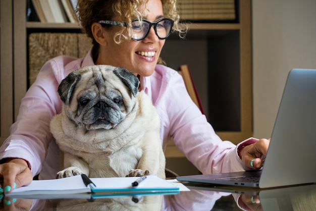 コンピューターで自宅で作業している一人の女性の肖像画-一緒に座っているかわいい子犬の犬-現代人と新しい仕事のライフスタイル-大人の女性の笑顔とオフィスでラップトップのディスプレイを見る