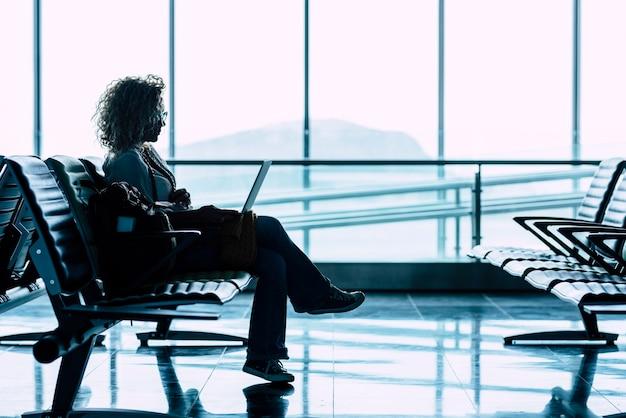 一人の女性が空港のゲートに一人で座って飛行機が旅行するのを待っています-ビジネスや休暇の人々が旅行します-背景の窓の明るい景色-座って待っている女性が出発飛行機を遅らせます