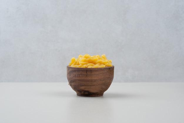 Одна деревянная миска, полная сырых макарон