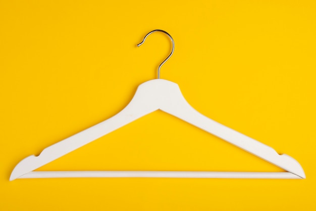 One wooden hanger isolated on yellow.